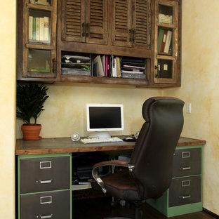 Foto di un piccolo ufficio mediterraneo con parquet scuro, nessun camino, pareti gialle, scrivania incassata e pavimento marrone