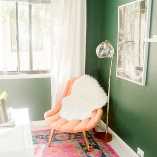 This is an example of a small eclectic home studio in San Francisco with green walls, carpet, a freestanding desk and pink floors.