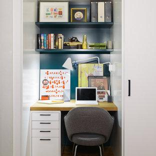 Esempio di un piccolo studio design con pareti blu, pavimento in legno massello medio e scrivania incassata