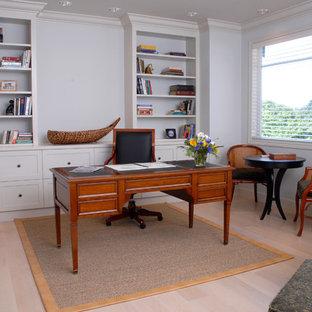 Idéer för ett stort amerikanskt hemmabibliotek, med vita väggar, ljust trägolv och ett fristående skrivbord