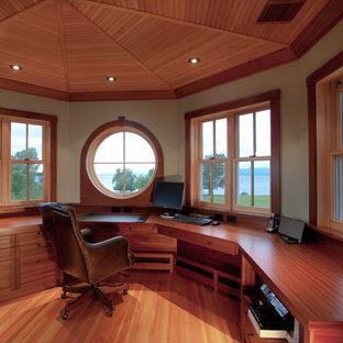 Idéer för ett stort maritimt hemmabibliotek, med beige väggar, ett inbyggt skrivbord och ljust trägolv