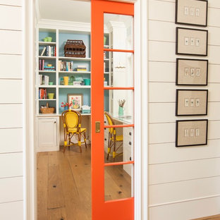 ロサンゼルスの小さいカントリー風おしゃれな書斎 (青い壁、淡色無垢フローリング、造り付け机、茶色い床) の写真