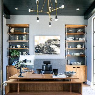 Bild på ett funkis hemmabibliotek, med grå väggar, heltäckningsmatta, en standard öppen spis, en spiselkrans i sten, ett fristående skrivbord och lila golv