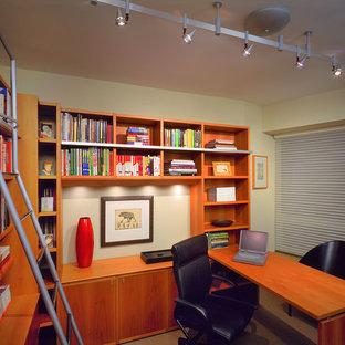 Esempio di un piccolo studio tradizionale con scrivania incassata, libreria, pareti beige, pavimento beige e nessun camino