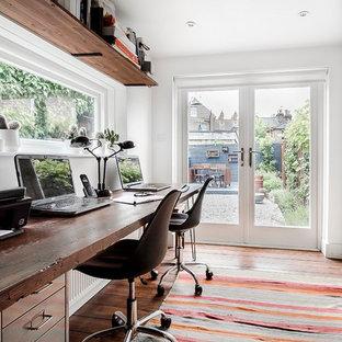 Immagine di un piccolo ufficio industriale con pareti bianche, parquet scuro, scrivania autoportante e pavimento marrone