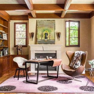 Bild på ett stort eklektiskt hemmabibliotek, med en standard öppen spis, en spiselkrans i betong, ett fristående skrivbord, beige väggar, mellanmörkt trägolv och brunt golv