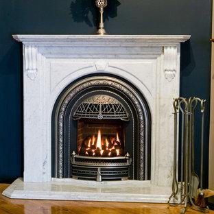 ソルトレイクシティのヴィクトリアン調のおしゃれなホームオフィス・書斎 (青い壁、無垢フローリング、標準型暖炉、石材の暖炉まわり) の写真