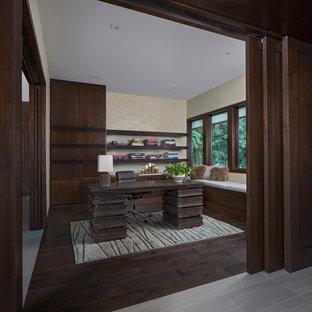 Bild på ett mellanstort funkis hemmabibliotek, med gröna väggar, mörkt trägolv, ett fristående skrivbord och brunt golv