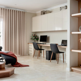 Inspiration for a mid-sized contemporary study room in Perth with beige walls, travertine floors, a built-in desk and beige floor.