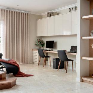 Ejemplo de despacho contemporáneo, de tamaño medio, con paredes beige, suelo de travertino, escritorio empotrado y suelo beige