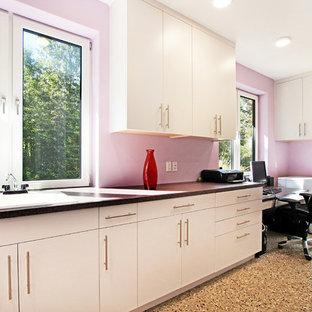 Ispirazione per una stanza da lavoro minimalista di medie dimensioni con pareti rosa, pavimento in cemento, scrivania incassata e pavimento multicolore