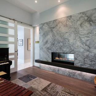 バンクーバーの中サイズのコンテンポラリースタイルのおしゃれなアトリエ・スタジオ (グレーの壁、無垢フローリング、両方向型暖炉、石材の暖炉まわり、茶色い床) の写真