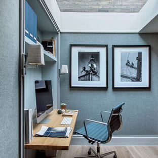 This is an example of a small modern home office and library with blue walls, light hardwood flooring, a built-in desk and beige floors.