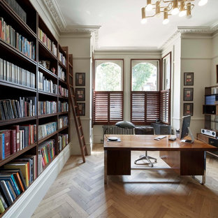 Transitional freestanding desk medium tone wood floor and beige floor home office photo in London with white walls