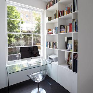 Modern inredning av ett litet arbetsrum, med vita väggar, mörkt trägolv och ett fristående skrivbord