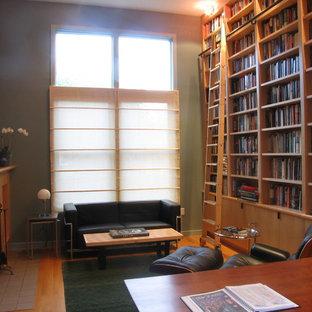 ボストンの中サイズのコンテンポラリースタイルのおしゃれなホームオフィス・仕事部屋 (ライブラリー、緑の壁、淡色無垢フローリング、標準型暖炉、木材の暖炉まわり、自立型机) の写真