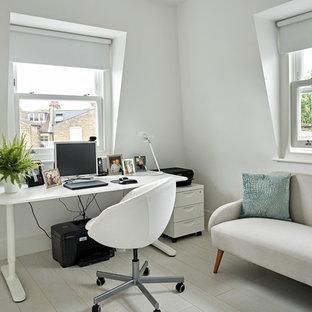 Modern inredning av ett mellanstort arbetsrum, med vita väggar, ljust trägolv, ett fristående skrivbord och vitt golv
