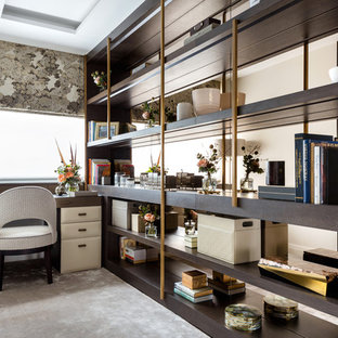 Inspiration for a traditional home office and library in London with carpet, a built-in desk and beige floors.