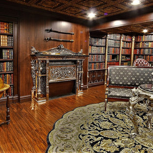 Large elegant built-in desk dark wood floor and brown floor home office library photo in Calgary with brown walls, a hanging fireplace and a brick fireplace