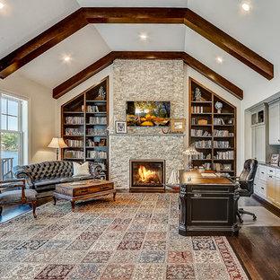 ミルウォーキーの巨大なビーチスタイルのおしゃれなホームオフィス・書斎 (ライブラリー、白い壁、濃色無垢フローリング、標準型暖炉、石材の暖炉まわり、自立型机、茶色い床) の写真