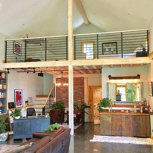 Esempio di un piccolo atelier rustico con pavimento in cemento, stufa a legna e pavimento grigio