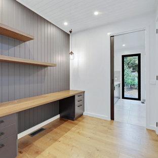 Inspiration för moderna hemmabibliotek, med vita väggar, ett inbyggt skrivbord och brunt golv