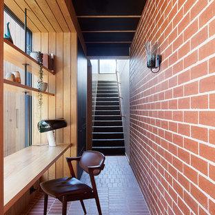 Cette photo montre un bureau rétro avec un mur rouge, un sol en brique, un bureau intégré et un sol rouge.