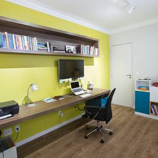 Kleines Modernes Arbeitszimmer mit grüner Wandfarbe, braunem Holzboden und Einbau-Schreibtisch in Sonstige