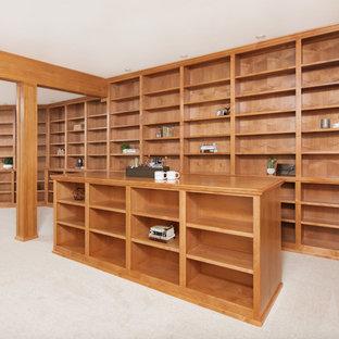 他の地域の中サイズのトラディショナルスタイルのおしゃれなホームオフィス・仕事部屋 (ライブラリー、ベージュの壁、カーペット敷き、暖炉なし、造り付け机、黒い床) の写真