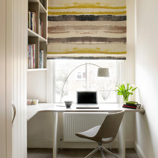 Inspiration for a contemporary home office and library in London with white walls, carpet, a built-in desk and beige floors.