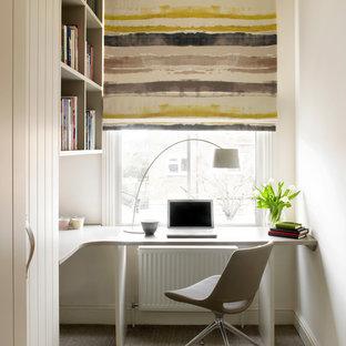 Ejemplo de despacho contemporáneo con paredes blancas, moqueta, escritorio empotrado y suelo beige