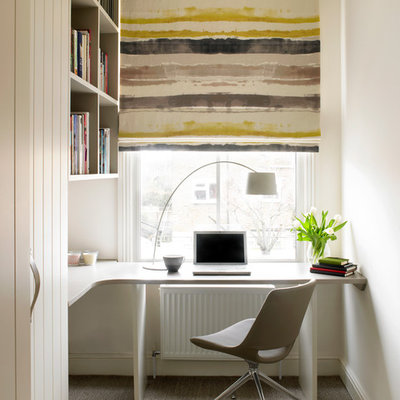 Home office - contemporary built-in desk carpeted and beige floor home office idea in London with white walls