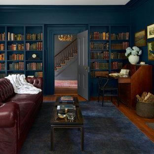 Imagen de despacho de estilo de casa de campo con paredes grises, suelo de madera en tonos medios, chimenea tradicional, marco de chimenea de madera y suelo azul