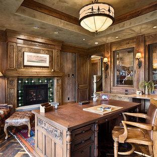 他の地域の広いトラディショナルスタイルのおしゃれな書斎 (茶色い壁、ラミネートの床、標準型暖炉、タイルの暖炉まわり、自立型机、茶色い床) の写真