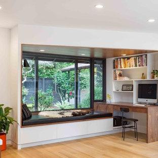 Bild på ett litet 60 tals arbetsrum, med ett bibliotek, vita väggar, ljust trägolv, ett inbyggt skrivbord och beiget golv