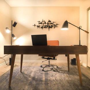 ロサンゼルスの小さいモダンスタイルのおしゃれな書斎 (グレーの壁、ラミネートの床、自立型机、グレーの床) の写真