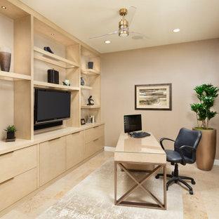 Inredning av ett modernt litet arbetsrum, med ett bibliotek, beige väggar, kalkstensgolv, ett fristående skrivbord och beiget golv