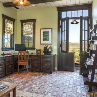 Immagine di un grande atelier stile americano con pareti verdi, pavimento in mattoni, nessun camino e scrivania incassata