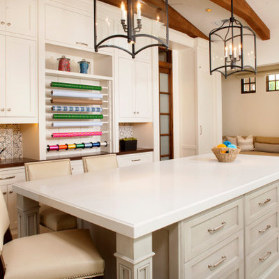 Transitional built-in desk medium tone wood floor and brown floor craft room photo in San Diego with white walls