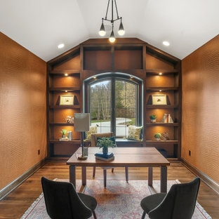 Example of a transitional freestanding desk medium tone wood floor, brown floor, vaulted ceiling and wallpaper study room design in Milwaukee with brown walls and no fireplace