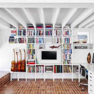 Идея дизайна: кабинет в современном стиле с библиотекой, белыми стенами, кирпичным полом, встроенным рабочим столом, красным полом и балками на потолке без камина