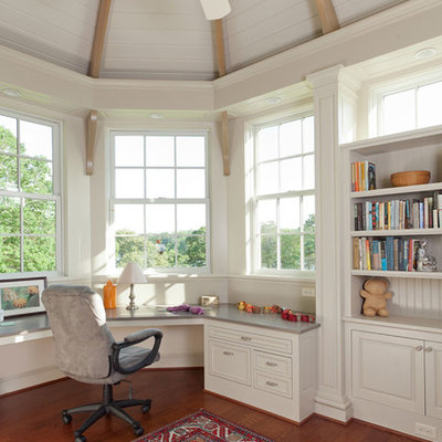 Example of a mid-sized classic built-in desk medium tone wood floor and brown floor study room design in San Francisco with white walls and no fireplace