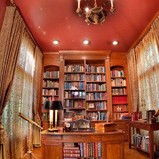 サンディエゴの中くらいのトラディショナルスタイルのおしゃれなホームオフィス・書斎 (ライブラリー、赤い壁、濃色無垢フローリング、暖炉なし、自立型机、茶色い床) の写真