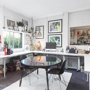 Idee per un atelier boho chic di medie dimensioni con pareti bianche, pavimento in cemento, scrivania incassata e pavimento nero