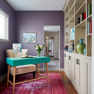 This is an example of a classic study in Denver with purple walls, dark hardwood flooring, a freestanding desk and brown floors.