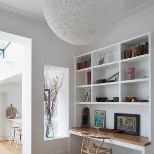 Mittelgroßes Modernes Arbeitszimmer mit Arbeitsplatz, weißer Wandfarbe, braunem Holzboden, Einbau-Schreibtisch und beigem Boden in London