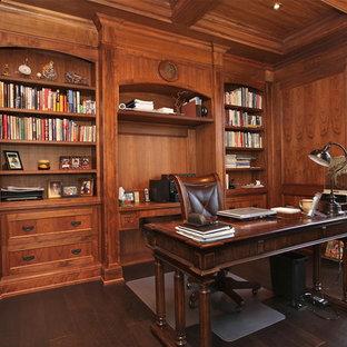 На фото: рабочее место среднего размера в классическом стиле с коричневыми стенами, темным паркетным полом, отдельно стоящим рабочим столом и коричневым полом