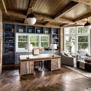 На фото: рабочее место в стиле кантри с серыми стенами, темным паркетным полом, фасадом камина из дерева, отдельно стоящим рабочим столом и горизонтальным камином с