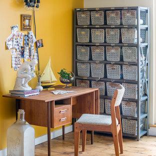 Eklektisches Arbeitszimmer mit gelber Wandfarbe, braunem Holzboden und freistehendem Schreibtisch in New York