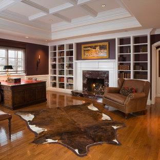 Exempel på ett klassiskt arbetsrum, med ett bibliotek, bruna väggar, mellanmörkt trägolv, en standard öppen spis och en spiselkrans i sten